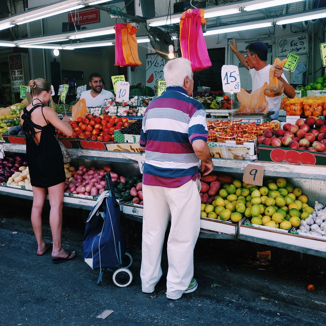 Woman and man buying fruit at a market stall