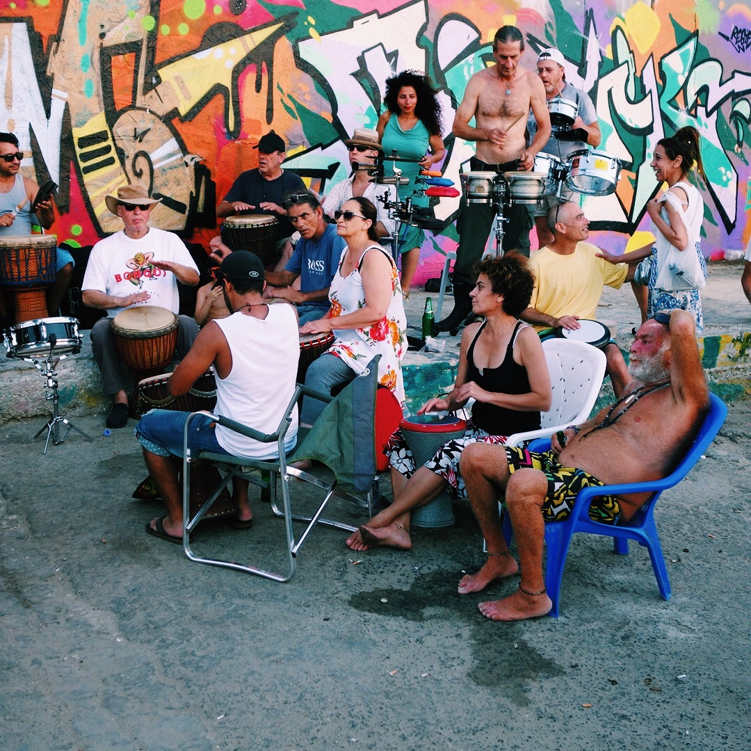 Group of people playing the drums in front of a graffiti wall