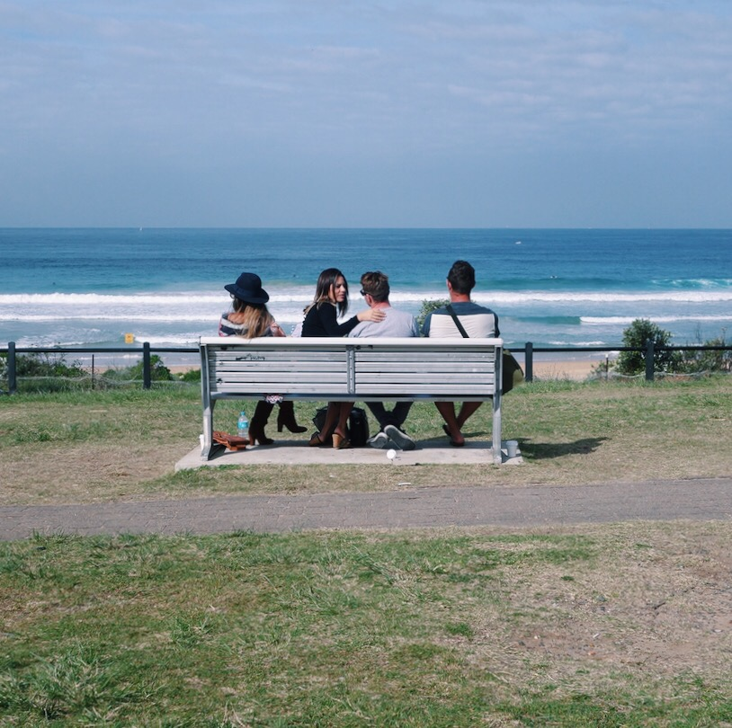 Friends sitting on a bench looking at the ocean