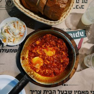 Pan of shakshuka, a little plate with pickled cabbage, and a basket of bread