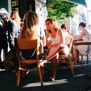 Couple of women sitting in the sunshine in a cafe