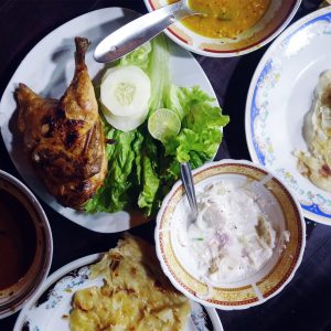 Dinner spread with chicken, dhal, onion-yoghurt salad, and flatbread